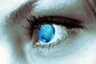 Woman's face with a globe superimposed over her eye
